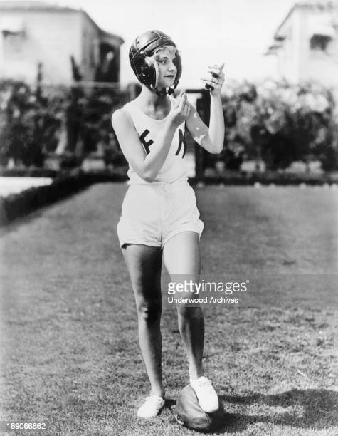 Aspiring actress Lola Holly pauses to powder her nose during a football scrimmage Hollywood California mid to late 1920s
