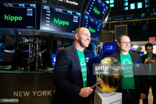Assaf Wand, chief executive officer of Hippo, left and Stewart Ellis, chief financial officer of Hippo, right, stand beside a ceremonial bell during...