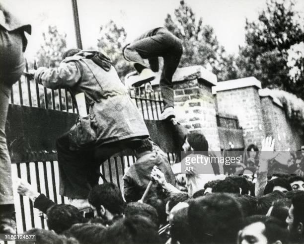 Assaillants escaladant les grilles au début de la prise d'otages de l'ambassade des EtatsUnis à Téhéran le 4 novembre 1979 Iran