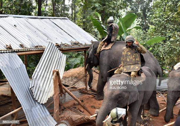 Assam forest department officials use an elephant to demolish illegal constructions inside the Amchan Wildlife Sanctuary during an eviction drive in...