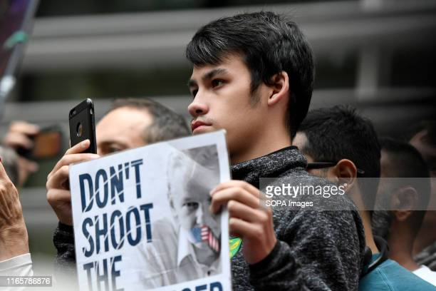 Assange supporter holds a placard that says Don't shoot the messenger during the rally in London Julian Assange supporters rally outside the British...