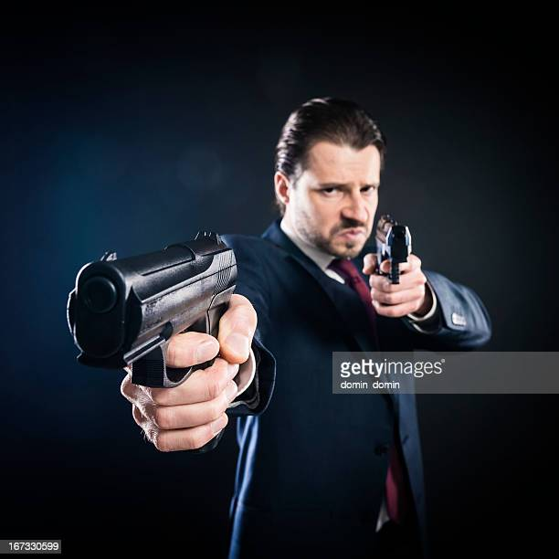 assassin, gangster suit aiming with two guns, mafioso, killer, mafia - serial killings stock pictures, royalty-free photos & images