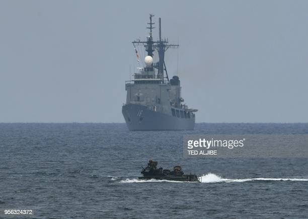 A US assault amphibious vehicle manoeuvers past Philippine navy's frigate Ramon Alcaraz during the amphibious landing as part of the annual...