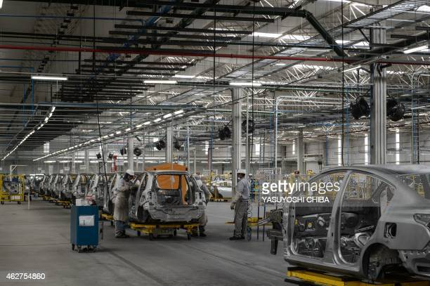 Assembled cars are carried by Automated Guided Vehicle a mobile robot that follows predetermined paths on the floor in the assembly line of the March...