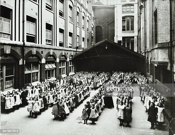 Assembly in the playground Jews' Free School Stepney London 1908 Girls line up for a mass assembly in the school playground Tall buildings surround...