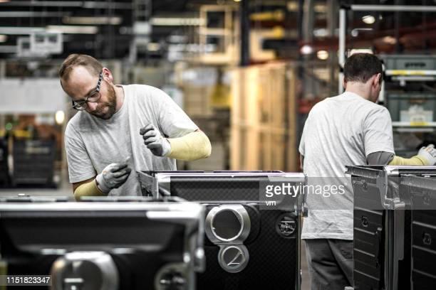 assemblagelijn werknemers construeren wasmachines - part of a series stockfoto's en -beelden