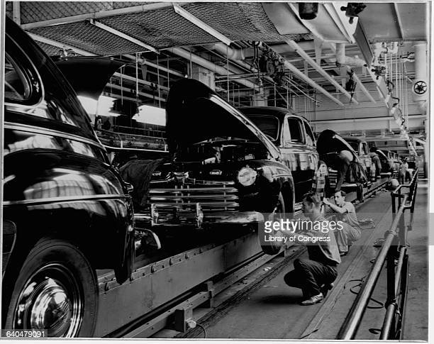 Assembly line workers put the finishing touches on automobiles being manufactured at a plant of the Ford Motor Company Detroit Michigan Circa 1930's