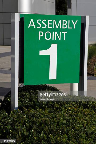 assembly point sign - evacuation stock pictures, royalty-free photos & images