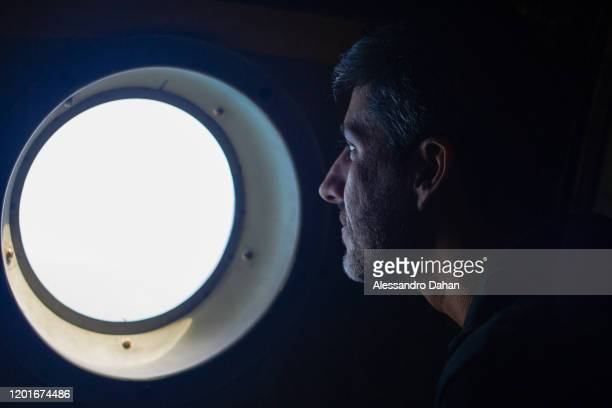 Assembly team member looking at new terrain through window during flight on November 04 2019 in King George Island Antarctica