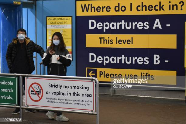 Assengers wait for departure at Manchester Airport, Manchester in north west England on March 17 as travel restrictions due to the novel coronavirus...