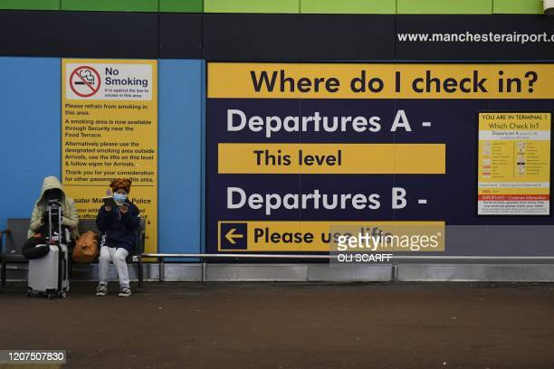 assengers wait for departure at Manchester Airport Manchester in north west England on March 17 as travel restrictions due to the novel coronavirus...
