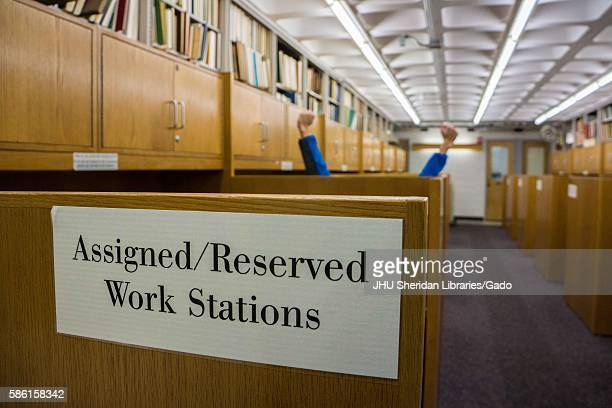 Assigned work stations, with one student raising his hands above the cubicle, in the Milton S. Eisenhower library on the Homewood campus of the Johns...
