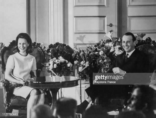Assis parmi les fleurs qui leur ont été offertes pour leurs fiançailles le prince Harald et Sonja Haraldsen à Oslo Norvège le 25 mars 1968
