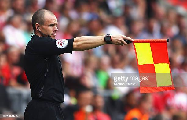 A assissant referee holds up the offside flag during the Premier League match between Southampton and Sunderland at St Mary's Stadium on August 27...