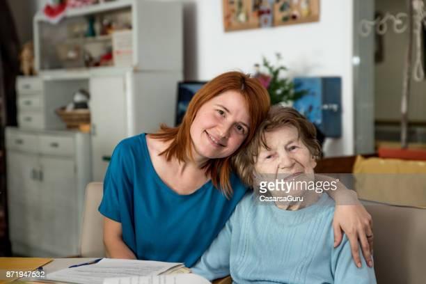 assistente presso nursing home hugging senior woman - al centro foto e immagini stock