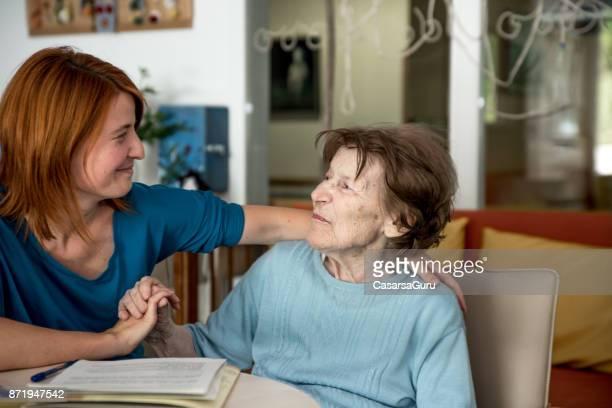assistente de repouso abraçando mulher sênior - assistente social - fotografias e filmes do acervo