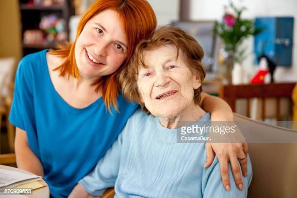 assistant at retirement home hugging senior woman - residential care stock photos and pictures