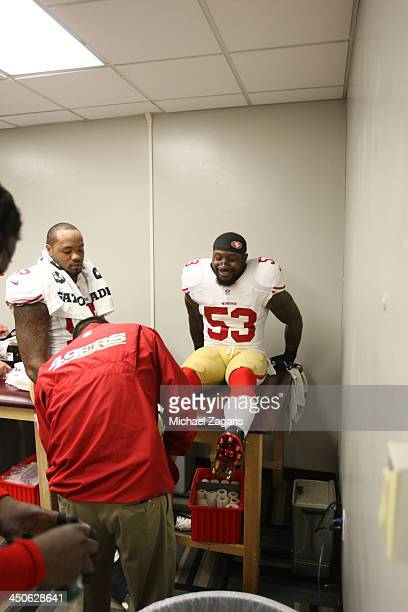 Assistant Athletic Trainer Manny Rivera of the San Francisco 49ers tapes up NaVorro Bowman as Ahmad Brooks looks on in the locker room prior to the...