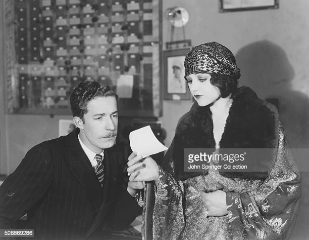 Assistant casting director Jack Votian giving actress Lolita Lee an OK slip for a costume at the wardrobe department of Paramount Hollywood studios