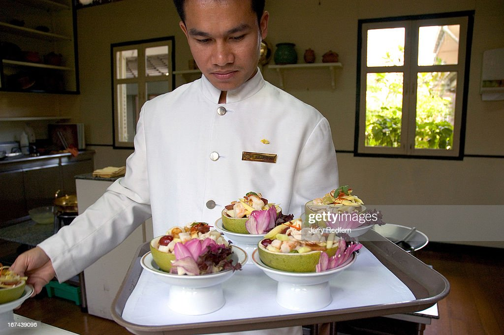Assistant chef Sudjarit gathers dishes prepared by students at the Thai Cooking School at the Oriental Hotel..