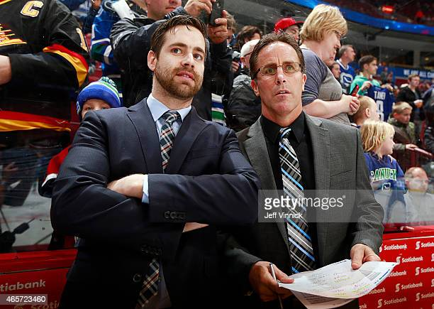 Assistant coach Ben Cooper and Assistant coach Doug Lidster of the Vancouver Canucks watch warmup for their NHL game against the Anaheim Ducks at...