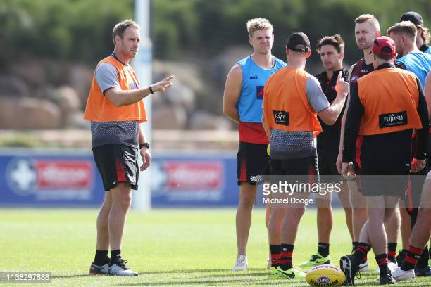 Assistant coach Brett Rutten speaks to players as fellow assistant coach James Kelly and Bombers head coach John Worsfold listen during an Essendon...