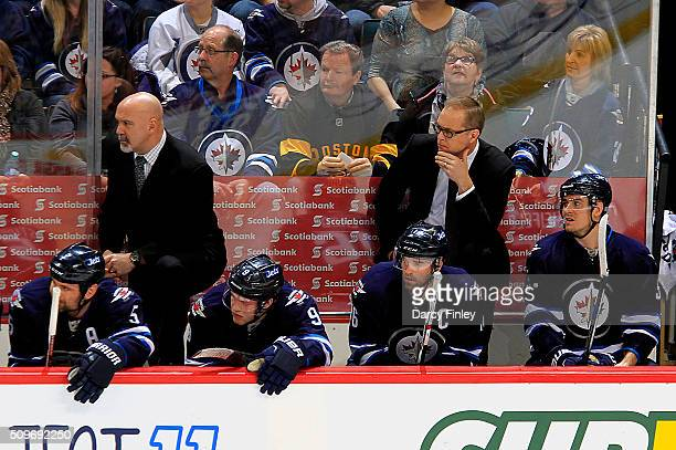 Assistant Coach Charlie Huddy and Head Coach Paul Maurice of the Winnipeg Jets look on from the bench during second period action against the Boston...