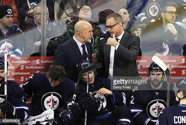 Assistant Coach Charlie Huddy and Head Coach Paul Maurice of the Winnipeg Jets discuss strategy during a second period stoppage in play against the...