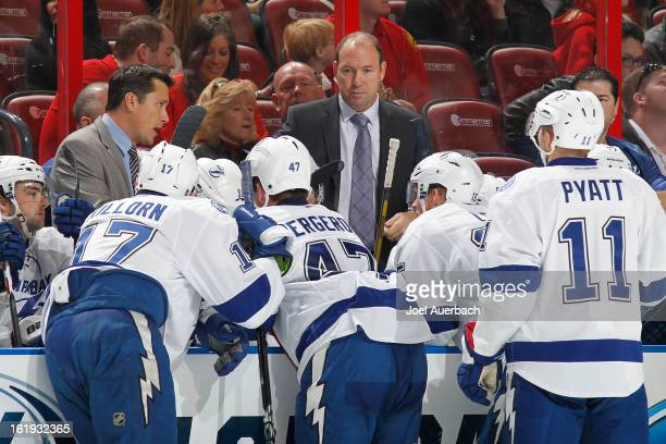 Assistant coach Daniel Lacroix looks on as head coach Guy Boucher of the Tampa Bay Lightning talks to the players during a time out against the...