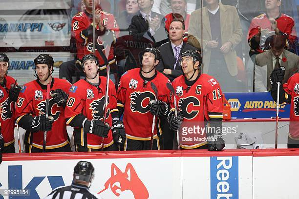 Assistant Coach Dave Lowry of the Calgary Flames and his players look up at the scoreboard during their game against the Detroit Red Wings on October...