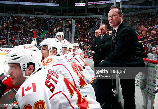 Assistant coach Dave Lowry of the Calgary Flames looks on from the bench during their NHL game against the Vancouver Canucks at Rogers Arena December...