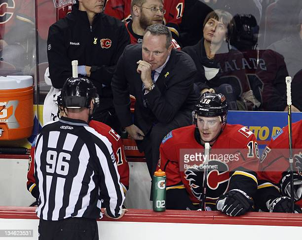 Assistant coach Dave Lowry of the Calgary Flames talks with linesman David Brisebois during the game against the Columbus Blue Jackets at the...
