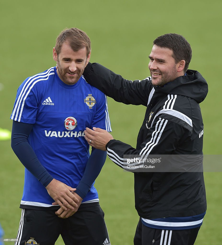 Assistant coach David Healy (R) embraces Niall McGinn (L) of Northern Ireland as the international football squad train on Bangor F.C's plastic pitch on September 1, 2015 in Bangor, Northern Ireland. Northern Ireland travel to face the Faroe Islands in a Euro 2016 Group F qualifiying game in Torshavn on Friday evening.