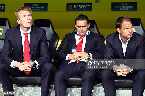 Assistant coach Dennis Bergkamp sporting dirctor Marc Overmars and head coach Frank De Boer of Amsterdam sit on the bench prior to the UEFA Champions...