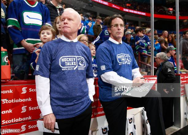 Assistant coach Doug Jarvis and assistant coach Doug Lidster of the Vancouver Canucks wear Hockey Talks tshirts on the bench before their NHL game...