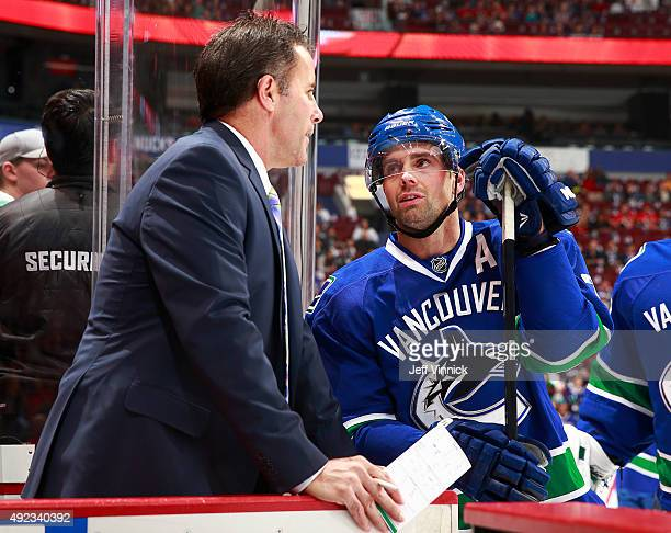 Assistant coach Doug Lidster of the Vancouver Canucks talks to Dan Hamhuis of the Vancouver Canucks during their NHL game against the Calgary Flames...