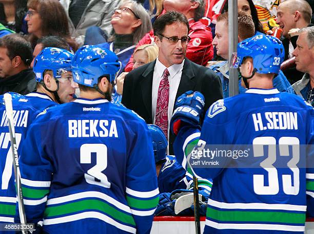 Assistant coach Doug Lidster of the Vancouver Canucks talks to players on the bench during their NHL game against the Montreal Canadiens at Rogers...