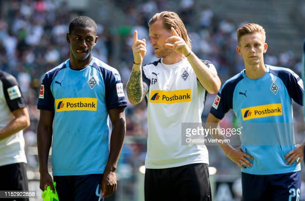 Assistant Coach Eugen Polanski of Borussia Moenchengladbach talks to Mamadou Doucoure during a Training Session of Borussia Moenchengladbach at...