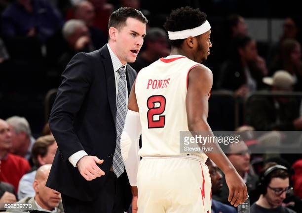 Assistant coach Greg St Jean of the St John's Red Storm speaks with Shamorie Ponds against the Iona Gaels during an NCAA men's basketball game at...