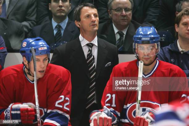 Assistant Coach Guy Carbonneau of the Montreal Canadiens stands behind Steve Begin and Chris Higgins the game against the Dallas Stars at the Bell...