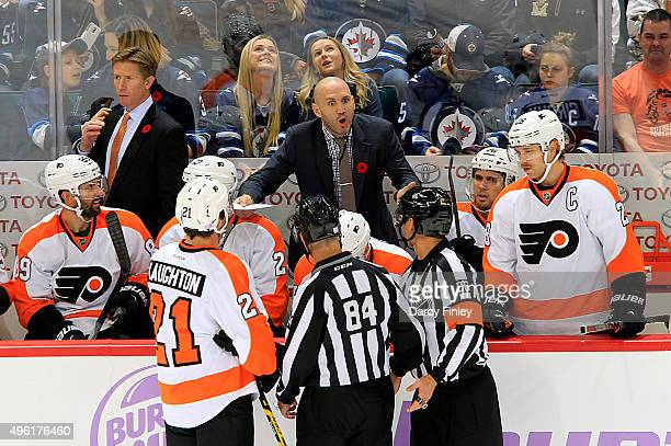 Assistant Coach Ian Laperriere of the Philadelphia Flyers exchanges words with referee Rob Martell during a first period stoppage in play against the...
