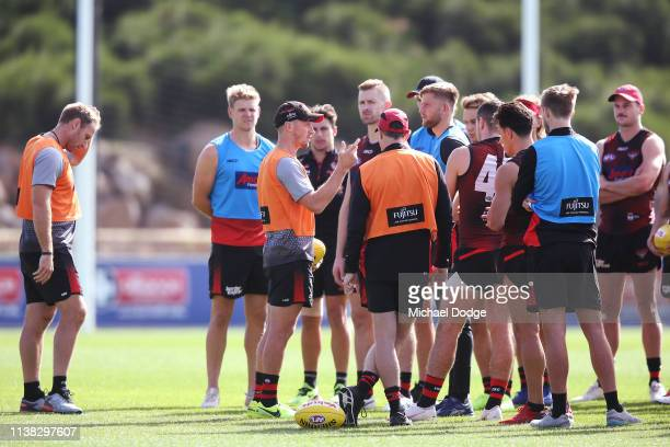 Assistant coach James Kelly speaks to players as fellow assistant coach Brett Rutten and Bombers head coach John Worsfold listen during an Essendon...