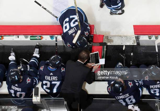 Assistant Coach Jamie Kompon and Patrik Laine of the Winnipeg Jets view a video replay on a tablet during a second period stoppage in play against...