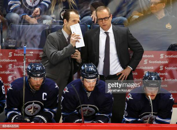 Assistant Coach Jamie Kompon of the Winnipeg Jets discusses strategy with Head Coach Paul Maurice during third period action against the Chicago...