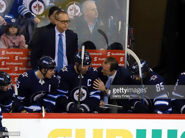 Assistant Coach Jamie Kompon of the Winnipeg Jets draws up a play at the bench for Mark Scheifele Blake Wheeler and Mathieu Perreault during a second...