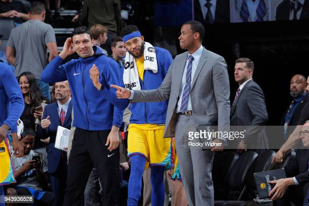 Assistant coach Jarron Collins JaVale McGee and Zaza Pachulia of the Golden State Warriors look on during the game against the Sacramento Kings on...