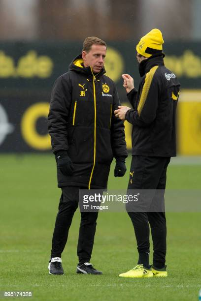 Assistant coach Joerg Heinrich of Dortmund speaks with Neven Subotic of Dortmund during a training session at BVB trainings center on December 13...