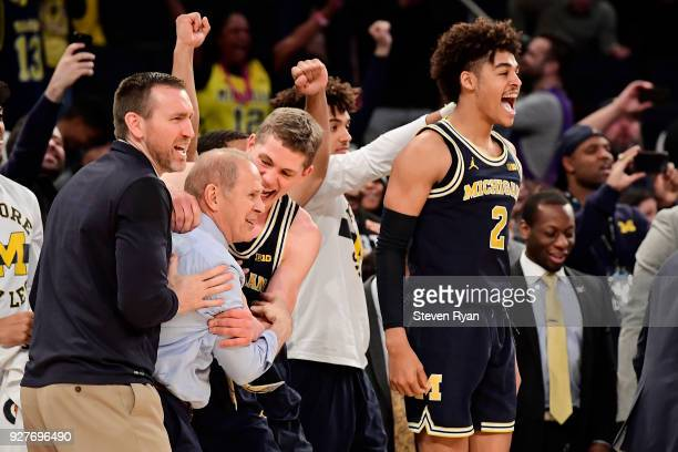 Assistant coach Jon Sanderson head coach John Beilein Moritz Wagner and Jordan Poole of the Michigan Wolverines celebrate a win over the Purdue...