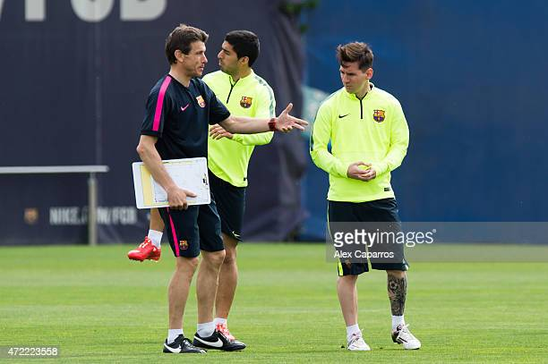Assistant coach Juan Carlos Unzue of FC Barcelona gives instructions to Lionel Messi during a training session ahead of their UEFA Champions League...