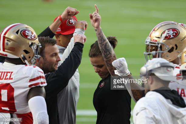 Assistant coach Katie Sowers and players of San Francisco 49ers huddle before Super Bowl LIV at Hard Rock Stadium on February 02 2020 in Miami Florida
